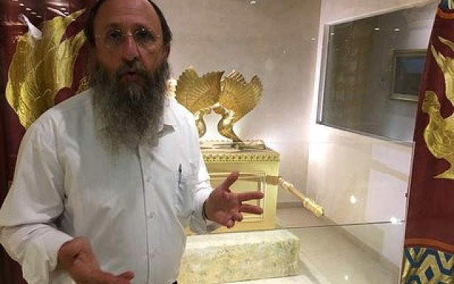 Rabbi Chaim Richman of the Temple Institute poses in front of a replica of the Ark of the Covenant in his group's exhibition in the Old City of Jerusalem last week.   Photo by Andrew Tobin