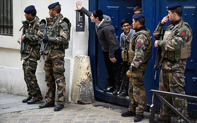 Children peer out from a doorway as armed soldiers patrol outside their school in the Jewish quarter of the Marais district in Paris.  Photo by Jeff J. Mitchell/Getty Images