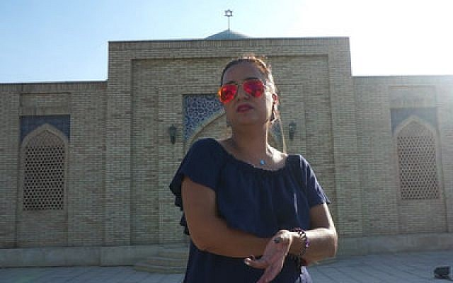"""Shirin Yakubov stands in front of Bukhara's Jewish cemetery in September. She saysthe Jewish community """"has no future"""" in the Uzbekistani city. Photo by Cnaan Liphshiz"""