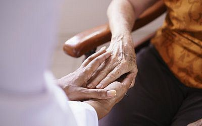 Black doctor visiting an aged patient, holding hands of a senior woman. Concept of comfort and compassion