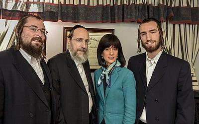 Rachel Freier poses for a photo in her Borough Park law office with (from left) nephew Shmuel Freier, husband David Freier and son Mayer Freier.  Photo by Andrew Katz
