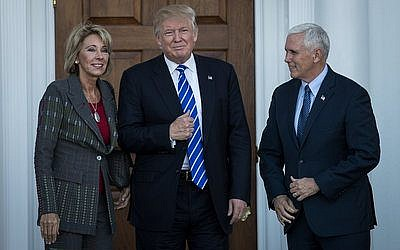 Betsy DeVos, President-elect Donald Trump and Vice President-elect Mike Pence pose for a photo outside the clubhouse at Trump International Golf Club in Bedminster Township, N.J. Photo by Drew Angerer/Getty Images