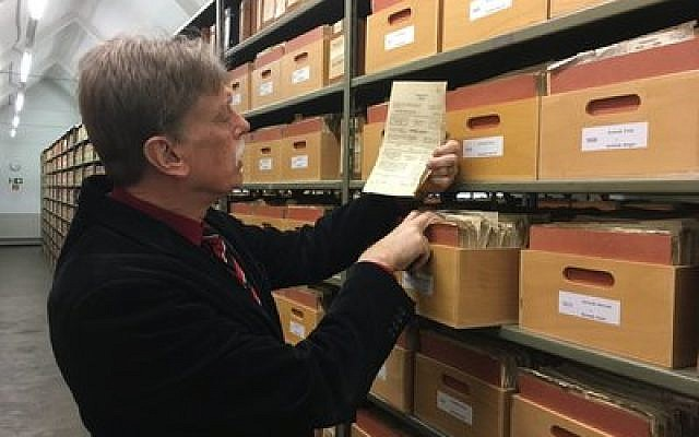 Hans-Hermann Söchtig, director of the German government agency Deutsche Dienststelle, examines a folder in the WASt archives, which help descendants  of Nazi soldiers learn more about their father's or grandfather's wartime service.   Photo by Orit Arfa