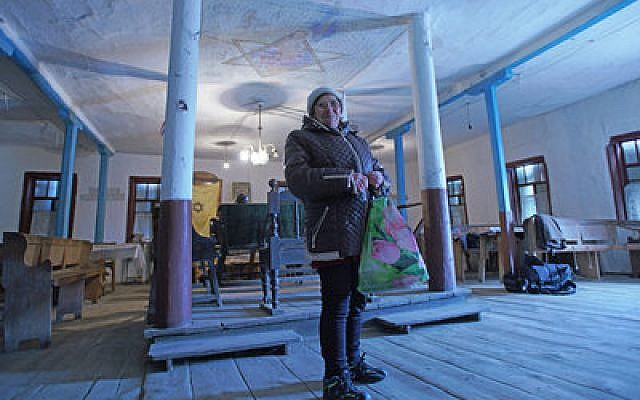 Bronia Feldman visits the synagogue in Bershad, Ukraine, where poverty in the Jewish quarter is the norm. Photo by Cnaan Liphshiz