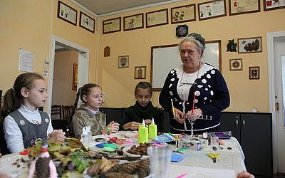 Irina Shlaeva, a social worker of Moldova's Jewish Family Service, and her students lighting Chanukah candles in Chisinau last December. Photo courtesy of JDC