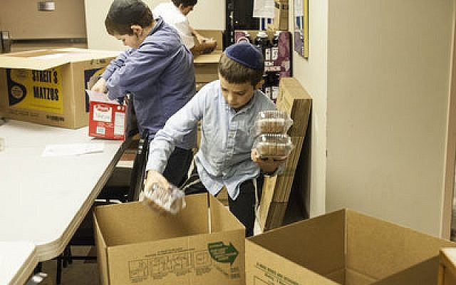 Students from Yeshiva Boys School packed food for inmates in correctional institutions and patients in state hospitals and group homes last week at the Aleph Institute.   Photo provided by Rabbi Moishe Mayir Vogel