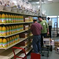 Shalom Pittsburgh volunteers Jon Halpern (left) and Greg Unatin stock shelves Sunday at the Squirrel Hill Community Food Pantry. (JF&CS photo)