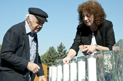 Holocaust survivor Moshe Baran and his daughter Avi Baran Munro, head of school at CDS, light a candle together.