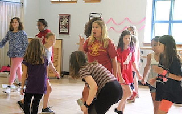 Performing Arts campers rehearse. Rachel Petro surrounded by angels and devils, is Mayor Matilda, the villain.   Photo courtesy of Jewish Community Center of Greater Pittsburgh