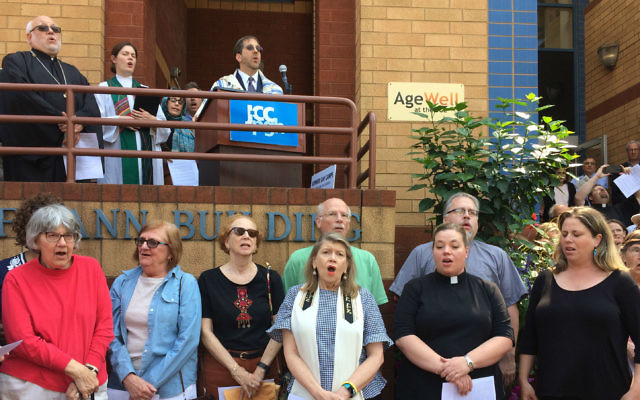 "Area clergy gather in front of the JCC, singing ""We Shall Overcome"" in a demonstration organized by the JCC's newly formed Center for Loving Kindness and Civic Engagement, and Christian Associates of Southwest Pennsylvania.	  Photo by Toby Tabachnick"