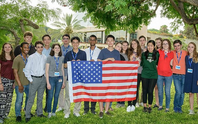 This year's U.S. delegation to the ISSI program poses for a photo on the Weizmann Institute's campus. Natalia Hajlasz is seventh from the right, behind the young man in the blue T-shirt who is holding the American flag; she is holding the right corner of the flag.    Photo courtesy of Kate Schmier