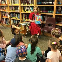 Hillel Academy librarian Bonnie Morris reads to a class of young students.     Photo by Toby Tabachnick