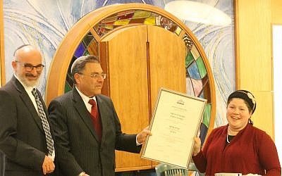 Rabbi Shuki Reich, left, seminary head of the Susi Bradfield Women's Institute of Halakhic Leadership, and Rabbi Shlomo Riskin, chancellor of Ohr Torah Stone, present Rabbanit Shira Zimmerman with her certification as a spiritual leader and arbiter of Jewish law at a ceremony in Jerusalem.    Photo courtesy of Ohr Torah Stone