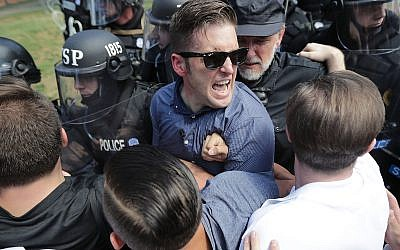 "White supremacist leader Richard Spencer, center, and supporters clash with police after the ""Unite the Right"" rally in Charlottesville, Va., in August. (Photo by Chip Somodevilla/ Getty Images)"