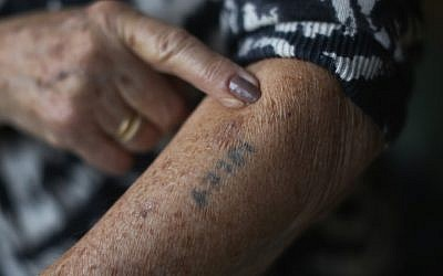 A Holocaust survivor shows her number tattoo. (Photo by Christopher Furlong/Getty Images)