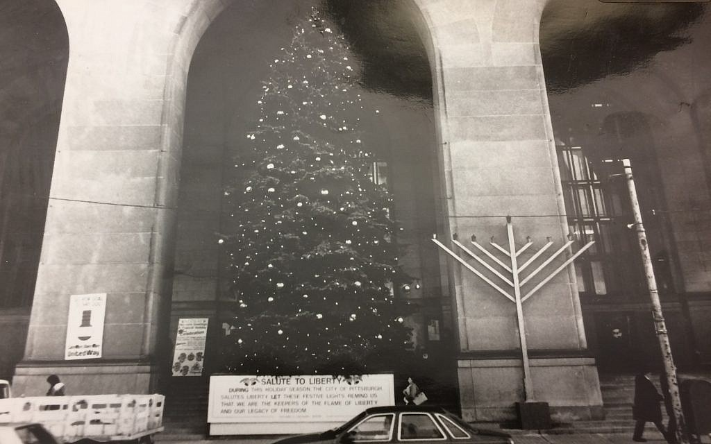 A photo exhibit of the menorah and Christmas tree on the steps of the City-County Building. (Photo by Toby Tabachnick)