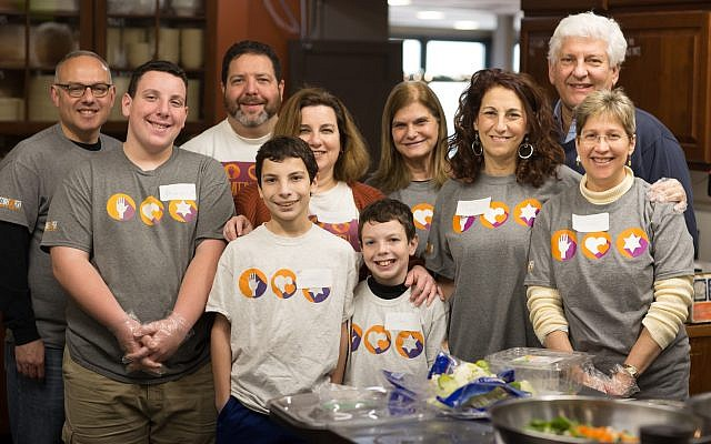 Feeding the hungry is a priority at Hot Metal Bridge Faith Community, South Side — a priority that Mitzvah Day volunteers, including Jewish Federation Board Chair Meryl K. Ainsman (back row, third from left) supported through action in the kitchen. (Photo by Josh Franzos)