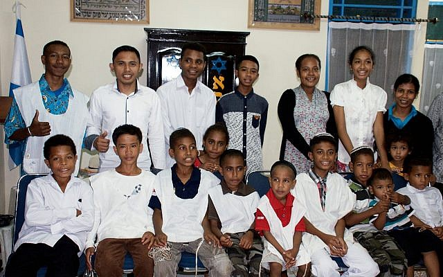 In the Papuan community, one of the communities that Temple Hadar Israel donated a Torah to, there is a Shabbat morning tradition in which the boys and young men wear arbah kanfot (a white four-cornered garment with special knotted strings at each corner) over their clothing during the service. (Photo by Rabbi David Kunin)