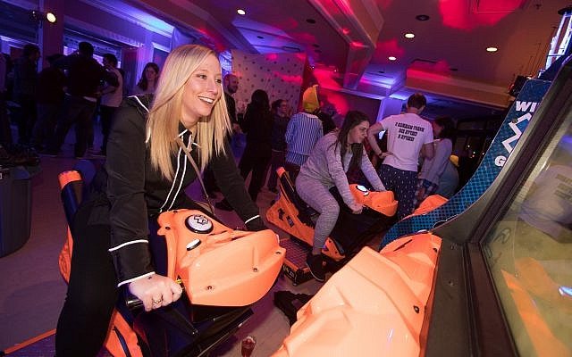 Marissa Karp puts her driving skills to the test as she rides one of the motorcycle simulators provided by Dave & Buster's. (Photo by Josh Franzos)