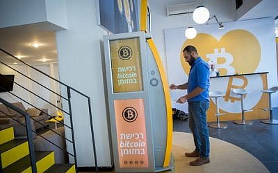 On Nov. 5, a man uses a bitcoin ATM machine at the Bitcoin Change center on Dizengoff Street in Tel Aviv. The center houses the ATM as well as a museum on the history of the cryptocurrency. (Photo by Miriam Alster / Flash90)