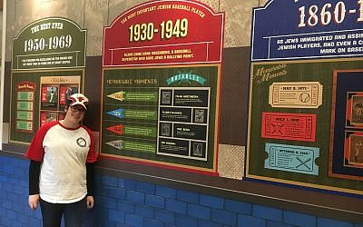 Deli worker Zahava Auerbach poses next to an exhibit at the Jewish baseball museum at Milt's Extra Innings in Chicago. (Photo by Ellen Braunstein)