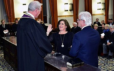 Supreme Court Justice Kevin M. Dougherty swears in Ellen Ceisler on a Bible held by her fiancé, Chris Gorson. (Photo courtesy of Ceisler campaign)