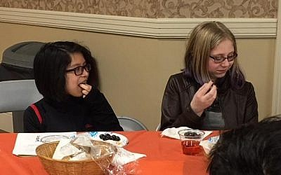 Hannah Dunn and Rebecca Gerse learn the correct blessing for eating olives at the Weiger School as part of its Tu B'Shevat  celebration. (Photo courtesy of Temple David)
