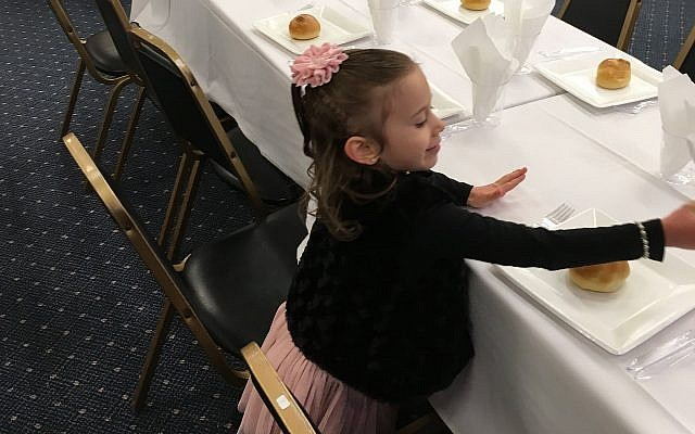 Leah Altein helps set tables for Chabad of Pittsburgh's first community Shabbat dinner in its new home on the corner of Forbes Avenue and Beechwood Boulevard. (Photo courtesy of Chabad of Pittsburgh)