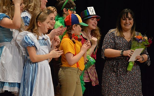 From left: Ada Perlman, Madison Zunder, Leah Heym (all dressed like Alice), Carly Caplan (next to Alice), Nadav Gilboa (green glasses), Jackie DeWitt (rainbow hat), Dori Catz (10/6 top hat), director Jessica Savitz. (Photo courtesy of Community Day School)