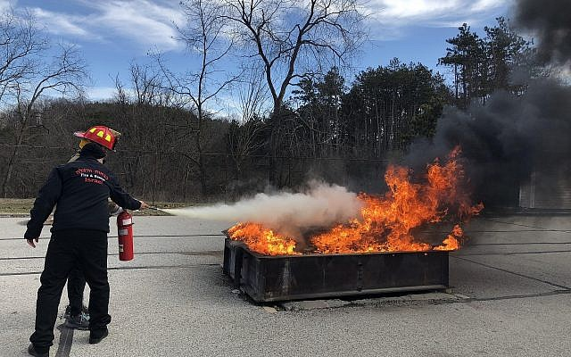 Volunteers practiced using a fire extinguisher at the Allegheny County Emergency Services Fire Academy Sunday. (Photo by Lauren Rosenblatt)