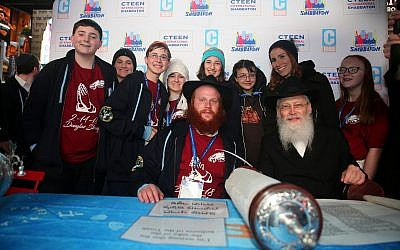 Chayale Denburg, standing second from right, and survivors of the Parkland, Fla., school shooting pose for a photo with Rabbi Shaya Denburg, seated left, and Rabbi Moshe Klein at Chabad's CTeen conference. (Photo by Itzik Roytman/CTeen)