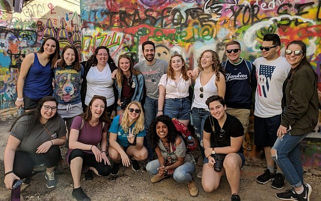 Participants pose for a photo during a graffiti tour in the Florentin neighborhood of Tel Aviv. (Photo courtesy of Brian Burke)