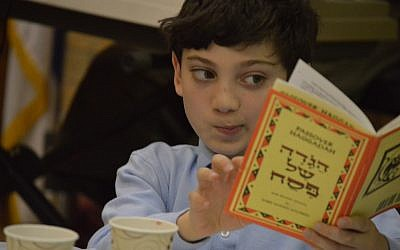 Third-grade student Jordan Block prepares to read from his Haggadah during the CDS Lower School model seder. (Photo courtesy of Community Day School)