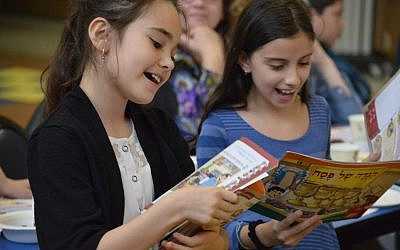 Fourth-grade students Roni Pishoto and Liron Ohayon sing the Four Questions at the CDS Intermediate School model seder. (Photo courtesy of Community Day School)