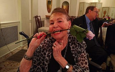 Thelma Gold Landay cheerily bites down on a rose that was given to her during the Steeltown Entertainment Project's celebration of mothers. (Photo by Adam Reinherz)