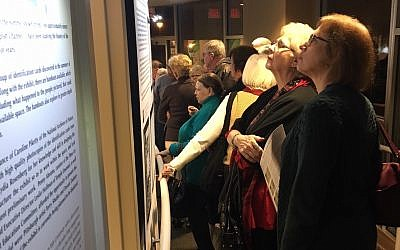 Patrons peruse David Rosenberg's research on the exhibit's opening day. (Photo by Lydia Rosenberg)