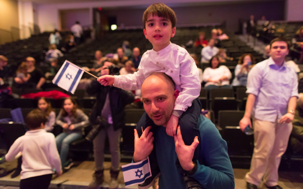 A father and son proudly wave Israeli flags during the Yom Ha'atzmaut celebration at the JCC in Squirrel Hill. (Photo by Josh Franzos)