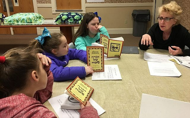 "Pati Eisenberg, Natalie Keough, Sara Pechersky and Anya Bakaturski check their haggadot for the words to ""Eliyahu HaNavi."" (Photo courtesy of Temple David)"