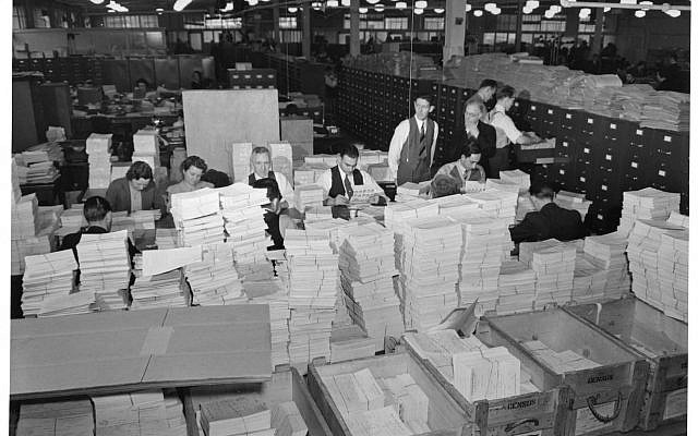 "This photo, which shows U.S. officials processing alien registration documents in 1940, is part of the ""Americans and the Holocaust"" exhibit. (Photo courtesy of U.S. Citizenship and Immigration Services History Office & Library)"