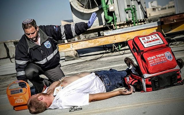 A volunteer treats an injured man. (Photo courtesy of United Hatzalah of Israel)