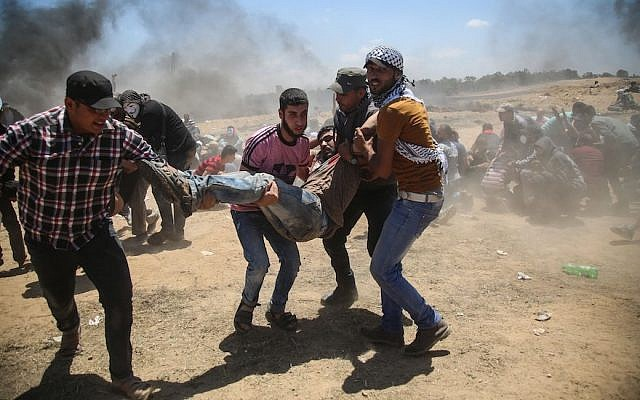 Palestinians carrying a wounded man during a protest against United States' plans to relocate its embassy from Tel Aviv to Jerusalem, near Al Bureij Refugee Camp at the Gaza-Israel border, May 14, 2018. (Photo by Hassan Jedi/Anadolu Agency/Getty Images)