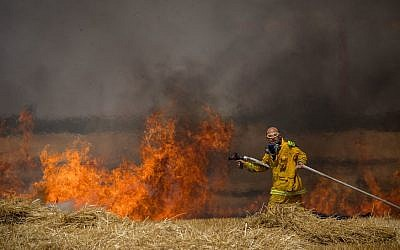 Israeli firefighters extinguish a fire in a wheat field caused from kites flown by Palestinian protesters, near the border with the Gaza Strip, May 30, 2018. (Photo by Yonatan Sindel/Flash90)