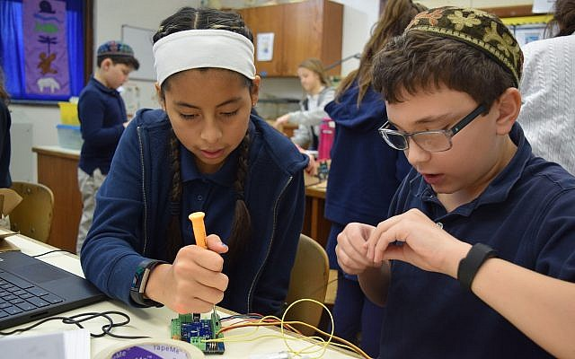 CDS fifth graders Maya Smith, left, and Jordan Sampson work to build and program robots they designed using upcycled materials and Hummingbird Robotics Kits through the school's Arts and Bots program. (Photo courtesy of Community Day School)