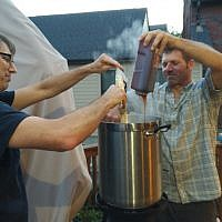 Justin Braver and Dan Gelman pour malt extracts into boiling water as part of the brewing process. (Photo by Adam Reinherz)