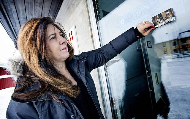 Carinne Sjoberg peeling off a sticker that neo-Nazis left on the door of what used to be the Jewish community center of Umea, Sweden. (Photo courtesy of Carinne Sjoberg)