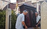 Tom Furstenberg, right, and a fellow congregant carry the Torah ark out of the Great Synagogue of Deventer last month. (Photo by Cnaan Liphshiz)