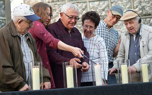 From left: Holocaust survivors Sam Gottesman, Harry Schneider and his wife, Patty Schneider, and Moshe Baran light memorial candles with the help of Lauren Bairnsfather, director of the Holocaust Center of Greater Pittsburgh. (Photo courtesy of Community Day School)