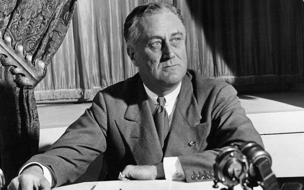 President Franklin D. Roosevelt seated at desk with microphones. (Photo from Wikimedia Commons)