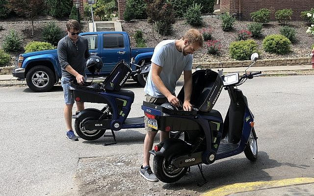 Mike Moran, left, CEO, and Jon Bametzreider, head technician, take helmets out of their company's scooters.(Photo by Lauren Rosenblatt)
