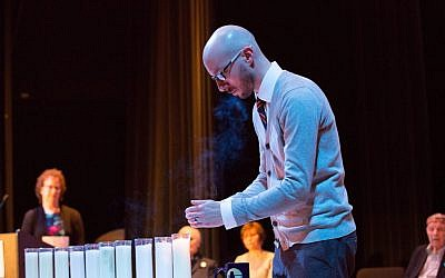 Nicholas Haberman, a teacher at Shaler Area High School, lights a candle at a Yom HaShoah commemoration. (Photo courtesy of the Holocaust Center of Pittsburgh)